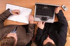 Hommes au-dessus du bureau avec l'ordinateur portatif et le calendrier en fonction Photos stock