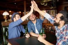 Hommes avec de la bière faisant la haute cinq à la barre ou au bar Photographie stock libre de droits