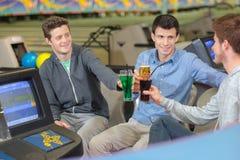 Hommes avec des boissons au centre de bowling Photos libres de droits