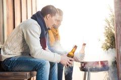 Hommes avec des bouteilles à bière sur le porche regardant le barbecue Image stock