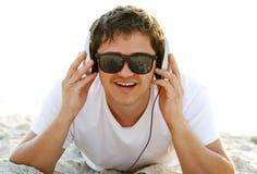 Hommes avec des écouteurs à la plage Photographie stock