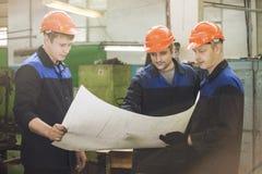 Hommes avec des dessins fonctionnant dans une vieille usine pour installer l'équipement image stock