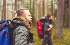 Hommes avec des sacs à dos et barbes augmentant dans la forêt Photos libres de droits