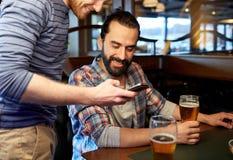 Hommes avec des smartphones buvant de la bière à la barre ou au bar Images libres de droits