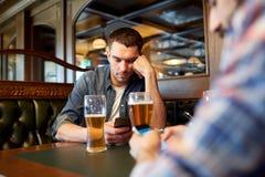 Hommes avec des smartphones buvant de la bière à la barre ou au bar Photographie stock libre de droits