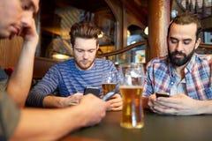 Hommes avec des smartphones buvant de la bière à la barre ou au bar Photo stock