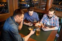 Hommes avec des smartphones buvant de la bière à la barre ou au bar Photo libre de droits