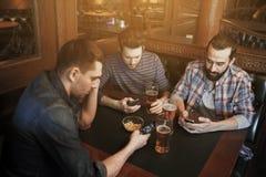 Hommes avec des smartphones buvant de la bière à la barre ou au bar Photos libres de droits