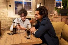Hommes avec des smartphones buvant de la bière à la barre ou au bar Photographie stock