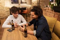 Hommes avec des smartphones buvant de la bière à la barre ou au bar Image stock