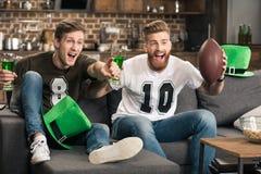 Hommes avec des verres de bière observant le match de football Image libre de droits