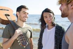 Hommes avec la guitare causant près de la mer Images libres de droits