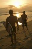 Hommes avec le coucher du soleil de observation de planche de surf à la plage Images stock