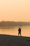 Hommes avec le détecteur de métaux dans le coucher du soleil Photo stock