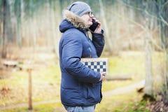 Hommes avec les amis de attente d'échecs et parler au téléphone intelligent Images libres de droits