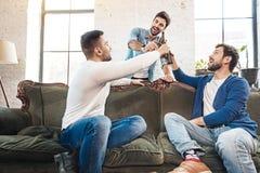Hommes avec plaisir gais soulevant des bouteilles avec de la bière Photos stock