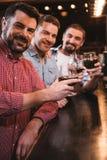 Hommes avec plaisir gais soulevant leurs verres Photos stock