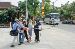 Hommes aveugles et femmes se tenant sur entre eux tout en marchant ensemble à travers la rue au Vietnam Image libre de droits