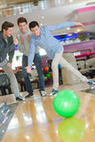 Hommes ayant l'amusement au centre de bowling Photographie stock