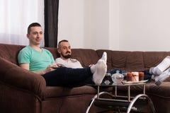 Hommes ayant l'amusement avec un nouveau jeu vidéo Photographie stock libre de droits