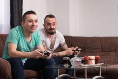 Hommes ayant l'amusement avec un nouveau jeu vidéo Photo stock
