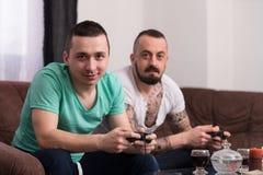 Hommes ayant l'amusement avec un nouveau jeu vidéo Photos stock