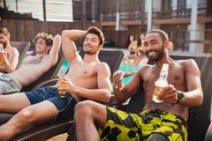 Hommes ayant l'amusement dans la piscine et buvant de la bière Image stock