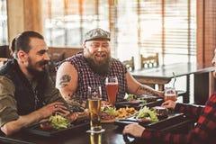 Hommes barbus heureux détendant dans le bar Photos stock