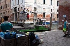 Hommes chargeant des déchets sur le bateau de déchets, Venise Photographie stock libre de droits