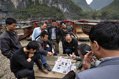 Hommes chinois, bateliers jouant le jeu de carte près du pilier, Guangxi, Chine Photos stock