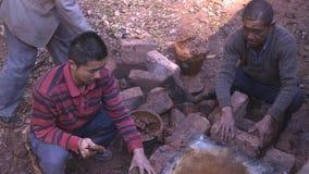 Hommes chinois construisant un fourneau de cuisinier par un courant, travaillant au gisement de sel yunnan La Chine images libres de droits