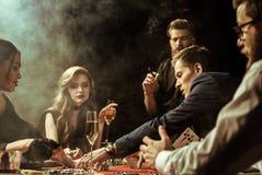 Hommes concentrés et femmes jouant le tisonnier dans le casino Images libres de droits