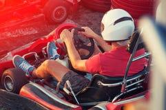 Hommes conduisant la voiture de kart avec la vitesse dans une voie d'emballage de terrain de jeu photographie stock