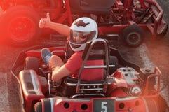 Hommes conduisant la voiture de kart avec la vitesse dans une voie d'emballage de terrain de jeu images stock