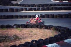 Hommes conduisant la voiture de kart avec la vitesse dans une voie d'emballage de terrain de jeu photo libre de droits