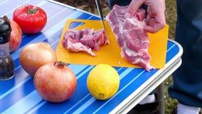 Hommes coupant en tranches la viande pour le BBQ