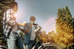 Hommes décontractés montant des bicyclettes et ayant le café Photos libres de droits