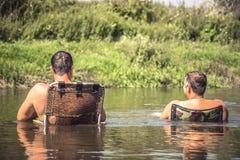 Hommes détendant dans l'eau régénératrice pendant leurs vacances de camping de loisirs sur la rivière et regardant sur le beau pa Image stock