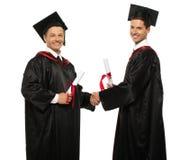 Hommes d'étudiant gradué se serrant la main Photos stock