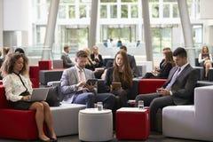 Hommes d'affaires à l'aide des dispositifs de Digital dans le lobby occupé de bureau image libre de droits