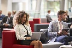 Hommes d'affaires à l'aide des dispositifs de Digital dans le lobby occupé de bureau image stock