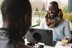 Hommes d'affaires à l'aide du mobile et de l'ordinateur portable dans le café Photo libre de droits