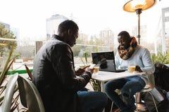 Hommes d'affaires à l'aide du mobile et de l'ordinateur portable dans le café Photographie stock libre de droits