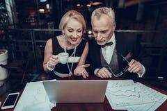 Hommes d'affaires âgés regardant dans l'ordinateur portable et le sourire images stock