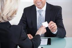 Hommes d'affaires échangeant la carte de visite dans le bureau images stock