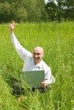 Hommes d'affaires adultes heureux avec l'ordinateur portatif gris photographie stock