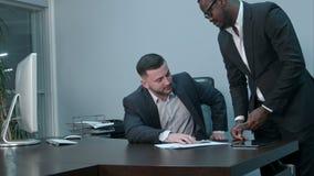 Hommes d'affaires afro-américains comptant l'argent sur le bureau et donnant des factures à son associé caucasien, elles se serra clips vidéos