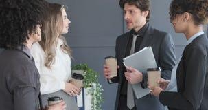 Hommes d'affaires agissant l'un sur l'autre tout en ayant le café dans le bureau banque de vidéos