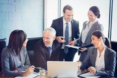 Hommes d'affaires agissant l'un sur l'autre dans la salle de conférence Photos stock