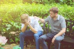 Hommes d'affaires américains consolant l'ami Jeune homme frustrant consolé par son ami Photographie stock libre de droits